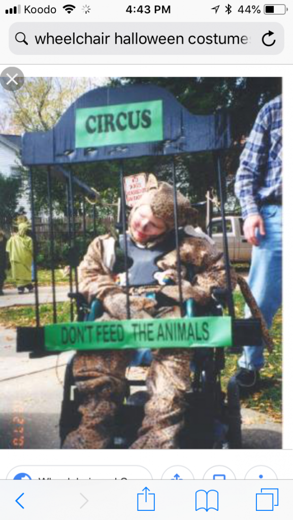 Child in a Halloween costume dressed as an animal in a cage with a sign above saying circus and below saying don't feed the animals.