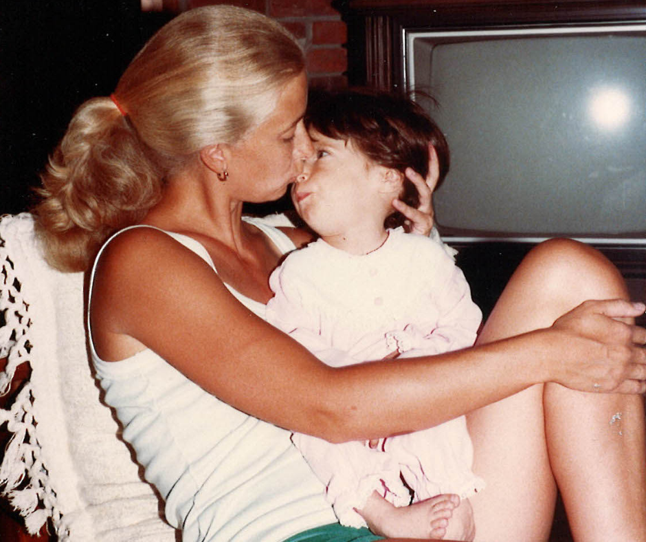 Linda gently holding Becky in their living room and kissing her nose.