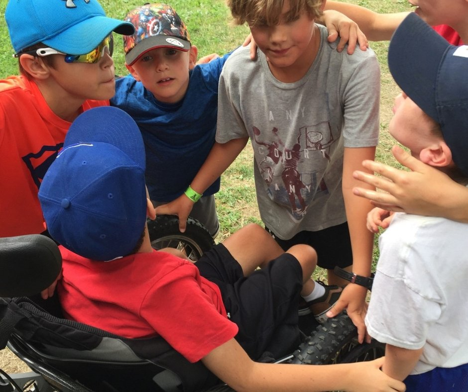 Children in a huddle at camp. One child using a wheel chair touches the arm of the child next to him.